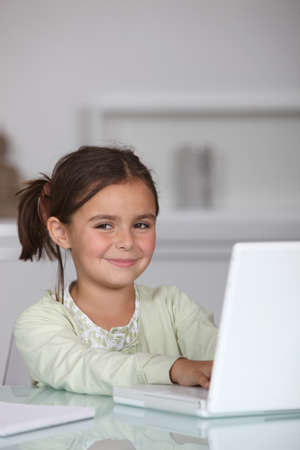 guardería: Niña sentada con laptop Foto de archivo