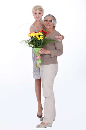 Woman giving her mother flowers photo
