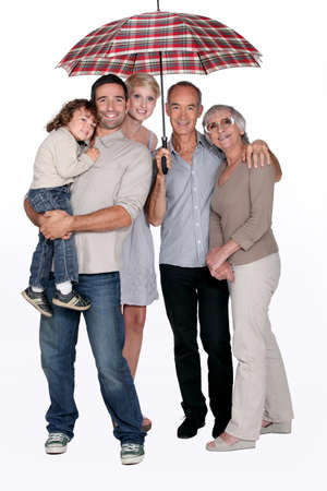 best protection: Smiling family under an umbrella Stock Photo