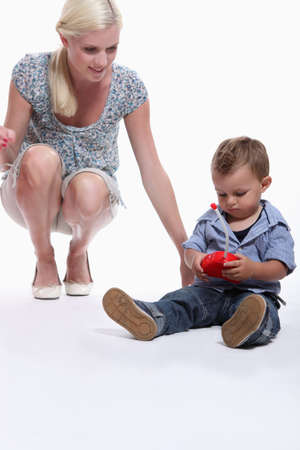 woman from behind: Mother playing with toddler