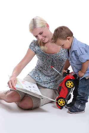 a mother showing a book to her little boy playing with a car photo