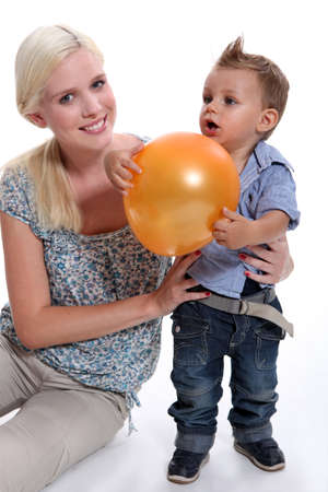 a mother and her little son playing with a balloon Stock Photo - 17732477