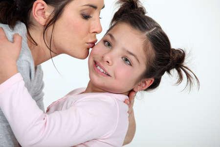 Woman kissing cute little girl photo