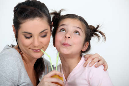 Mother and daughter sharing a drink photo