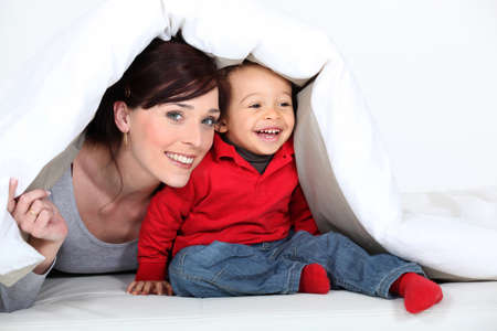 hide and seek: Woman and child hiding under a duvet Stock Photo
