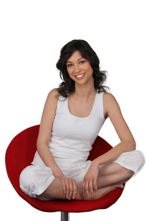 Woman in white sitting cross legged in a red chair photo