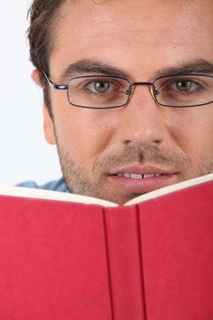 sexy teacher: Man in glasses reading a red hardback book Stock Photo