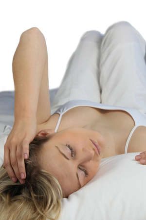 drowse: Blonde woman wearing white and lying on a white bed