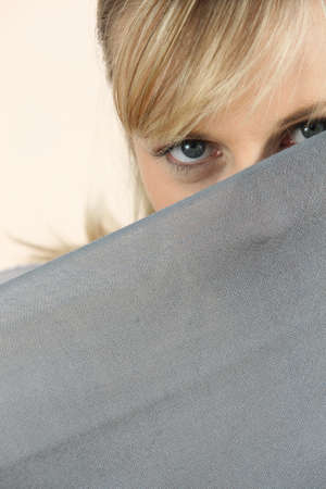 Young blond woman observing behind sheet photo