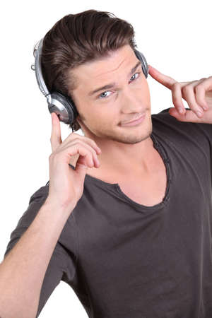 smirk: Man listening to music through headphones Stock Photo