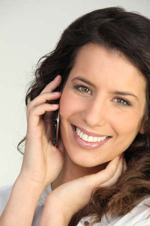 available time: Brunette woman on the phone Stock Photo