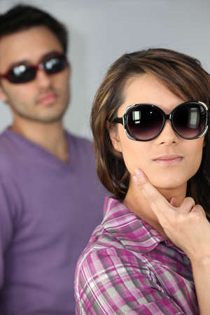dissimulation: young woman and man wearing sunglasses Stock Photo