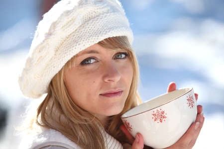 Woman drinking hot mug of coffee on a winters day photo