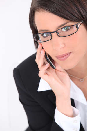 sleek: Smart young woman wearing glasses and using a sleek cellphone Stock Photo