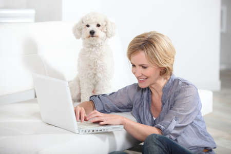 Woman using laptop computer next to small white dog photo