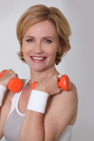 Blond woman in sportswear holding weights photo