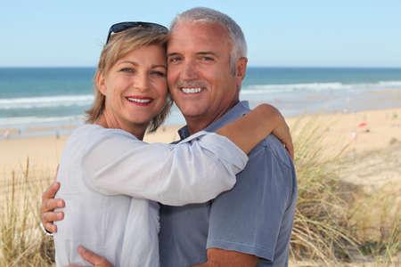 senior couple on vacation embracing photo