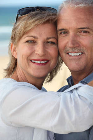 happy mature couple at beach photo