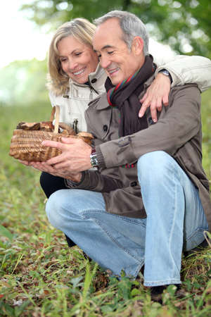 pasturage: old couple watching a wickerwork basket of mushrooms in the countryside Stock Photo