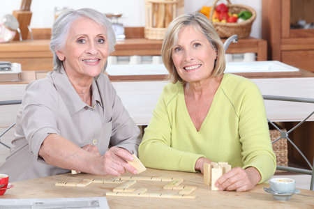 duo of retired ladies playing scrabble in the kitchen photo