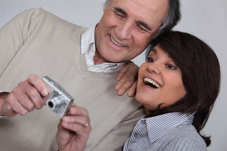 mature couple taking a picture of themselves with compact digital camera photo
