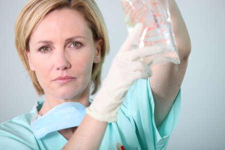 intravenous: Hospital nurse attending to a drip bag Stock Photo