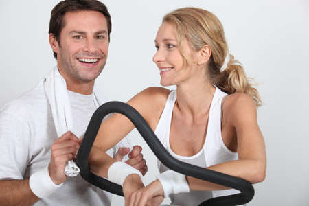 static bike: Couple at the gym on cycling machine
