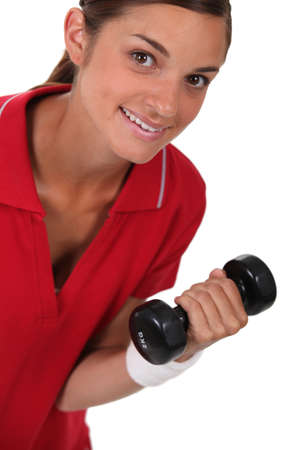 collarbone: Woman lifting a dumbbell Stock Photo