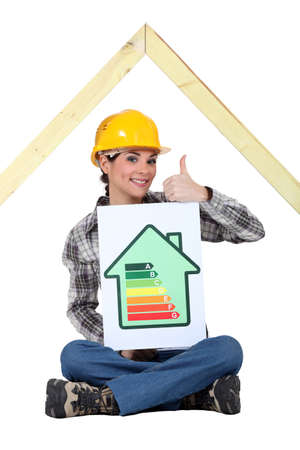 Female housebuilder with an energy rating sign Stock Photo - 17904075