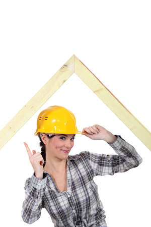 Carpenter standing under a wooden frame and shaking her finger Stock Photo - 17904071