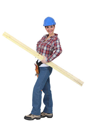servicewoman: portrait of young female carpenter holding lumber