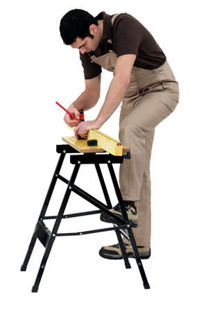 Workman marking a measurement on a wooden plank Stock Photo - 17904001
