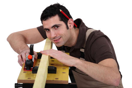 workbench: Carpenter eyeing a piece of wood Stock Photo