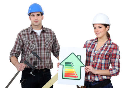 workwoman: Construction workers holding an energy efficiency rating chart and a clamp