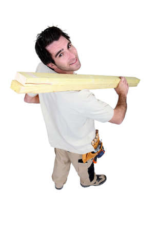 High-angle shot of a handyman carrying wooden planks photo
