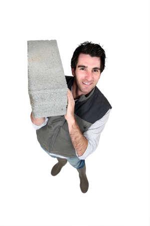 burdensome: Man carrying breeze block Stock Photo