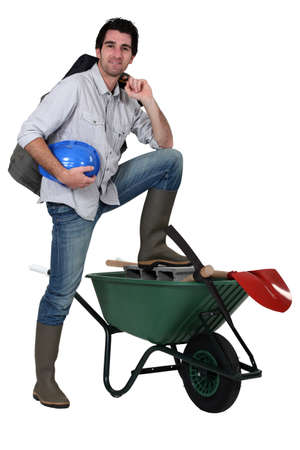 Tradesman with his foot propped up on a wheelbarrow photo