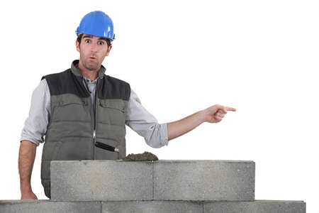 Shocked builder stood by wall pointing photo