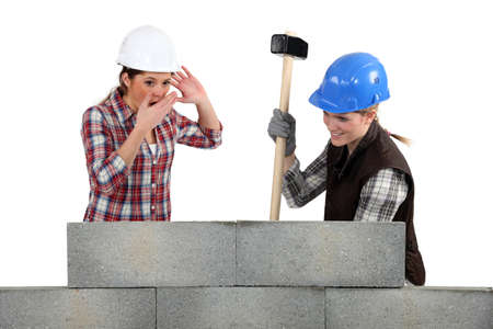 destroying: Two women smashing wall Stock Photo