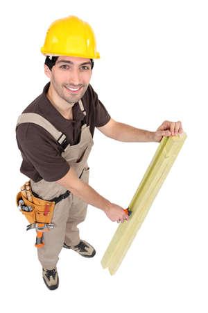 woodworker: Carpenter measuring plank of wood