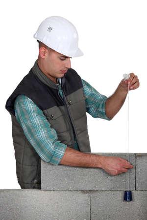 layers levels: Mason using plumb line, studio shot Stock Photo