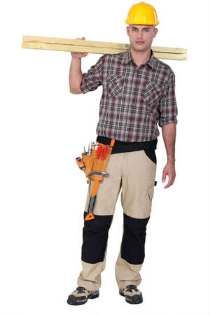 erecting: Man carrying two wooden plans over shoulder Stock Photo