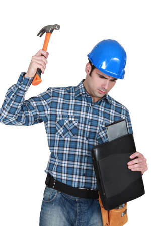 Man hammering a laptop computer photo