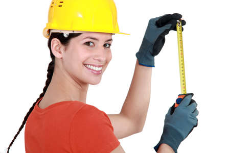 delimit: Young female laborer using measuring tape Stock Photo
