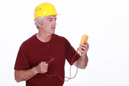 Tradesman looking at his multimeter's display Stock Photo - 17904218