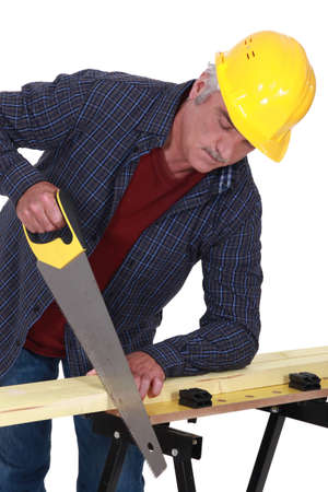 crosscut: Construction worker sawing a plank of wood