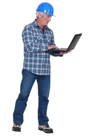 middle aged craftsman standing with laptop Stock Photo