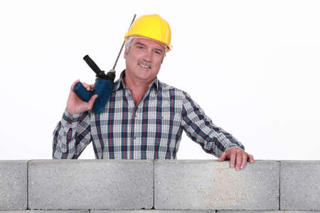 Builder stood by wall with power drill photo