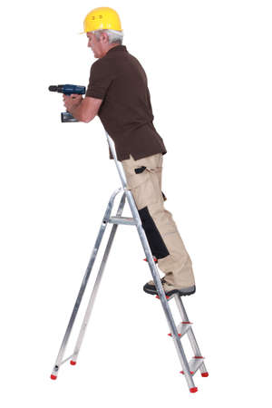 Tradesman standing on a stepladder and using a power tool photo