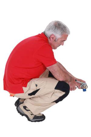 en cuclillas: Hombre con unos alicates